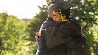 father hugging graduate son, diverse family